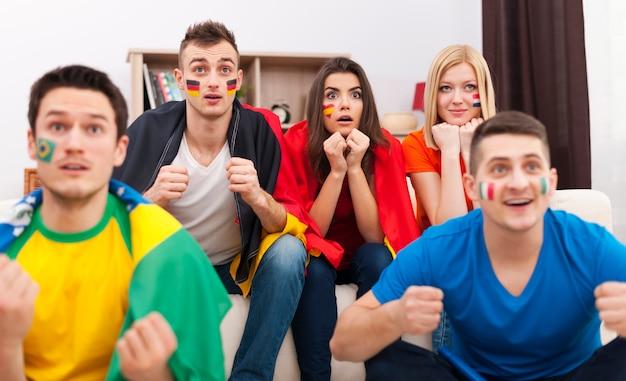 Retrato de jóvenes aficionados al fútbol durante la visualización del partido en la televisión