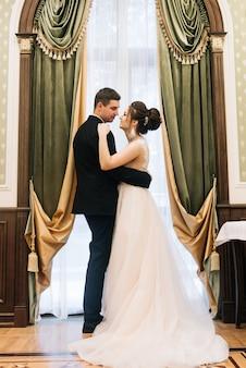 Retrato de jóvenes amantes felices de la novia y el novio en un lujoso interior cerca de la ventana. día de la boda