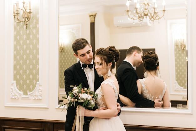 Retrato de jóvenes amantes felices de la novia y el novio en un lujoso interior. día de la boda