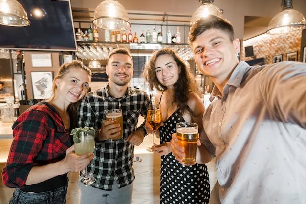 Retrato de jóvenes amigos sosteniendo vasos de bebidas en el bar