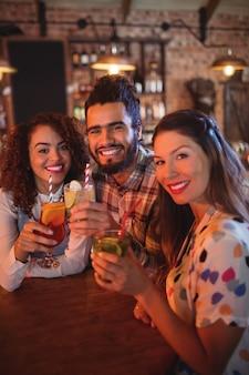 Retrato de jóvenes amigos tomando bebidas