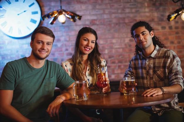 Retrato de jóvenes amigos tomando un cóctel