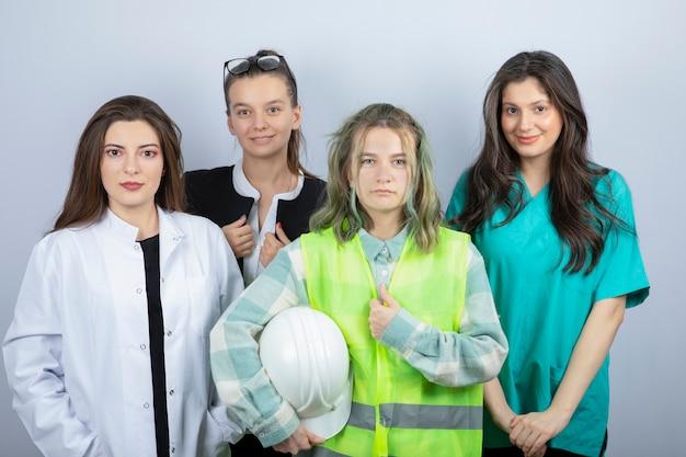 Retrato de jóvenes de diferentes profesiones de pie y posando sobre fondo blanco. foto de alta calidad