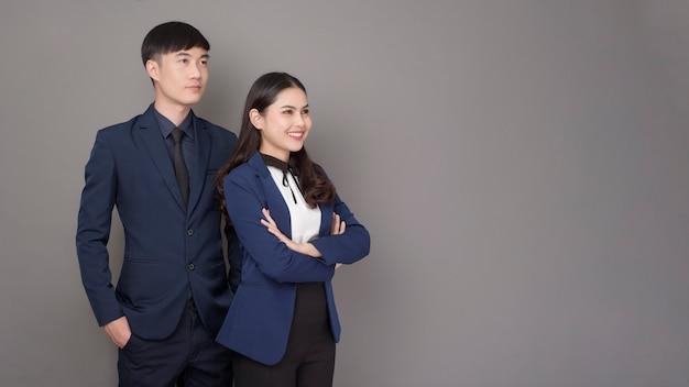 Retrato de jóvenes empresarios asiáticos de confianza sobre fondo gris