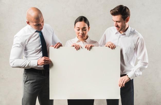 Retrato de jóvenes empresarios mirando gran cartel en blanco de pie contra la pared gris