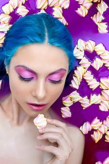 El retrato de jóvenes forma a la mujer atractiva de lujo con el pelo azul que se relaja en bañera.