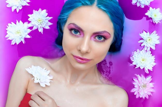 El retrato de los jóvenes forma a la mujer con el pelo azul que se relaja en bañera.