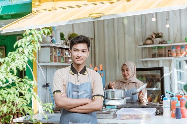 Retrato de jóvenes hombres y mujeres musulmanes que venden alimentos y bebidas con contenedor