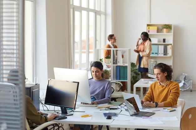 Retrato de jóvenes programadores de ti que utilizan computadoras mientras trabajan en el desarrollo de software en el interior de la oficina, espacio de copia