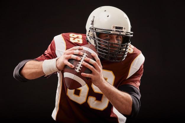 Retrato del jugador de fútbol americano que sostiene una pelota con ambas manos