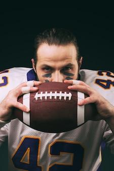 Retrato del jugador de fútbol americano sosteniendo una pelota y mirando