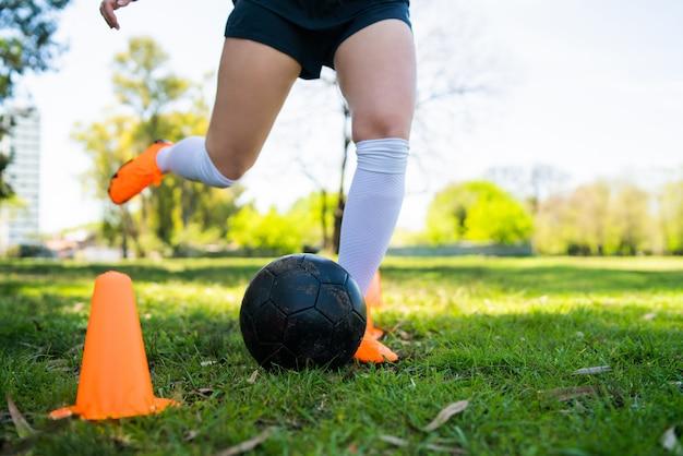 Retrato del jugador de fútbol femenino joven que corre alrededor de conos mientras que practica con la bola en campo. concepto deportivo