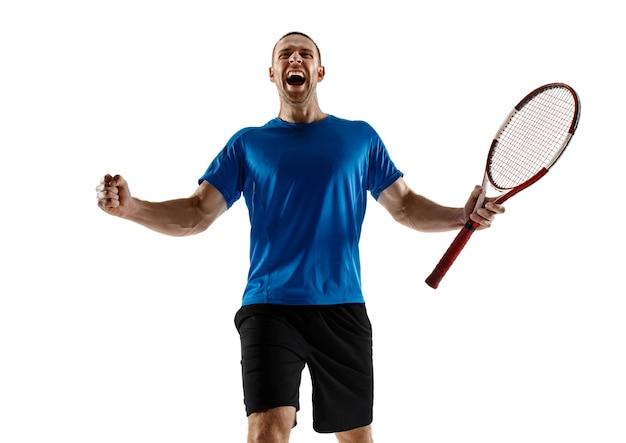 Retrato de un jugador de tenis masculino guapo celebrando su éxito aislado en una pared blanca. las emociones humanas, ganador, deporte, concepto de victoria