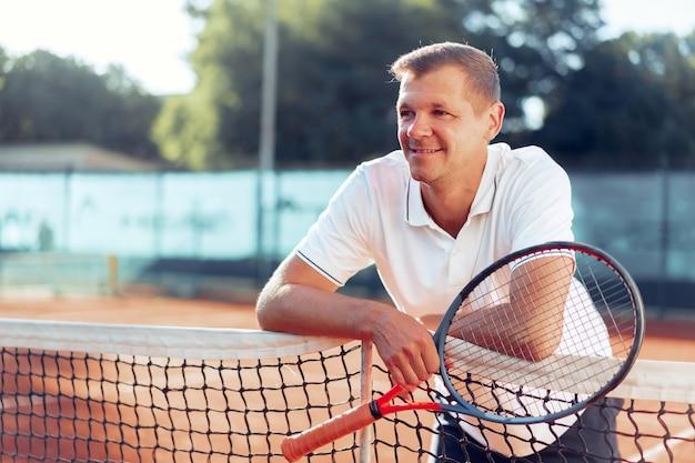 Retrato de jugador de tenis masculino positivo con pie de raqueta en la cancha de arcilla
