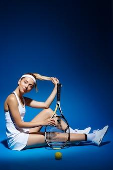 Retrato de una jugadora de tenis con raqueta y pelota sentado en el piso