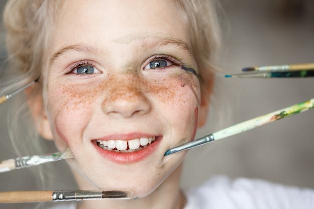 Retrato de juguetona chica rubia europea con pecas y pintura en la cara, jugando con pinceles. muchacha bastante alegre rubia que sonríe con los dientes.