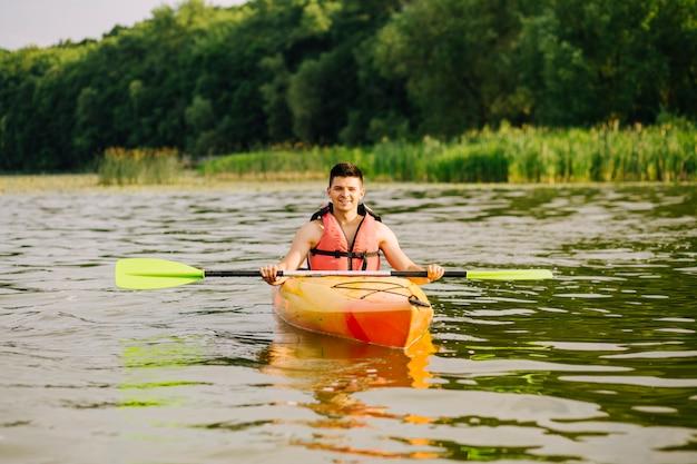 Retrato de kayakista masculino flotando en la superficie del agua