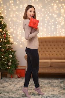 Retrato de labios rojos de joven feliz mirando caja de regalo envuelta.
