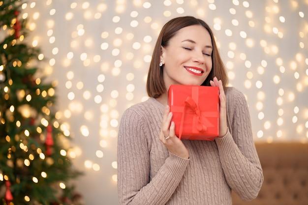 El retrato de los labios rojos de la mujer joven feliz es tan feliz de conseguir la caja de regalo envuelta.