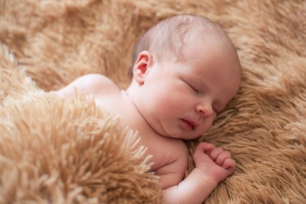 Retrato lacónico de lindo bebé recién nacido acostado con los ojos cerrados y durmiendo en la manta suave y esponjosa