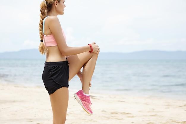 Retrato de lado de atractiva mujer deportiva con trenza larga que se extiende en la playa contra el mar azul