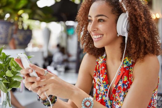 Retrato de lado de feliz estudiante afroamericana con piel oscura aprende idiomas extranjeros en audiolibros descargados en teléfonos inteligentes