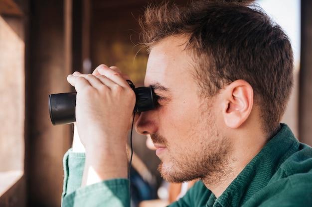 Retrato de lado de un hombre mirando a través de binoculares