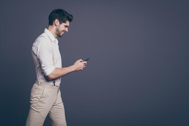 El retrato del lado del perfil de un chico positivo imponente ir a caminar usa el teléfono celular charlando con amigos leyendo noticias de las redes sociales y usa ropa elegante