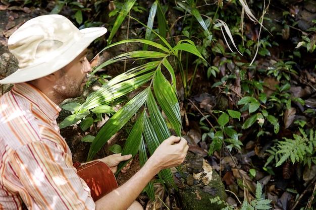 Retrato lateral del ecologista caucásico de mediana edad con maletín estudiando hojas de plantas exóticas verdes mientras realiza estudios ambientales al aire libre, explorando las condiciones de la naturaleza en la selva tropical