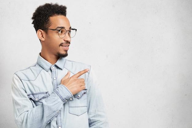 Retrato lateral de inteligente inteligente joven tiene bigote, barba y peinado afro, mira con perplejidad a un lado