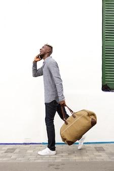 Retrato lateral de un joven africano que viaja caminando y hablando por teléfono celular