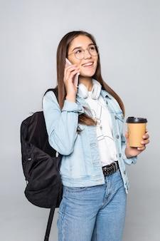 Retrato lateral de mujer joven estudiante hablar con teléfono inteligente, sosteniendo café para llevar taza aislado en la pared gris