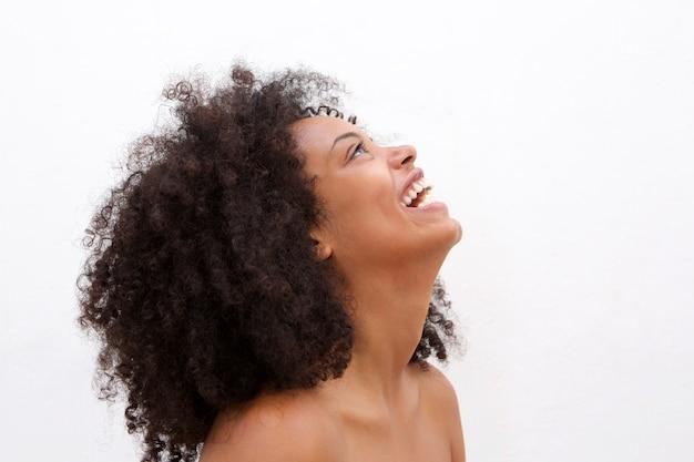 Retrato lateral de risa mujer negra con hombros descubiertos