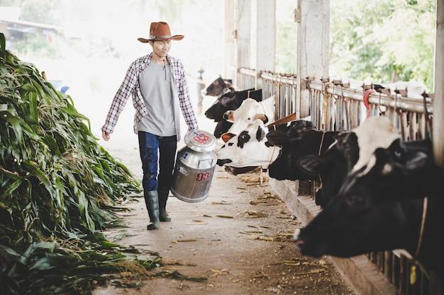 Retrato de un lechero guapo caminando con un recipiente de leche al aire libre en la escena rural