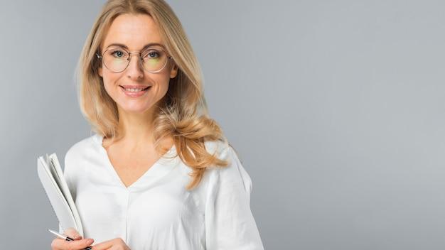 Retrato de las lentes que llevan de una empresaria joven que sostienen el papel y la pluma contra fondo gris