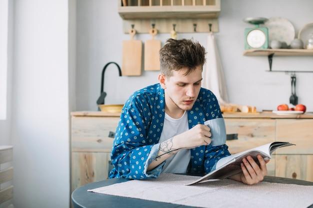 Retrato del libro de lectura del hombre mientras que bebe el café en cocina