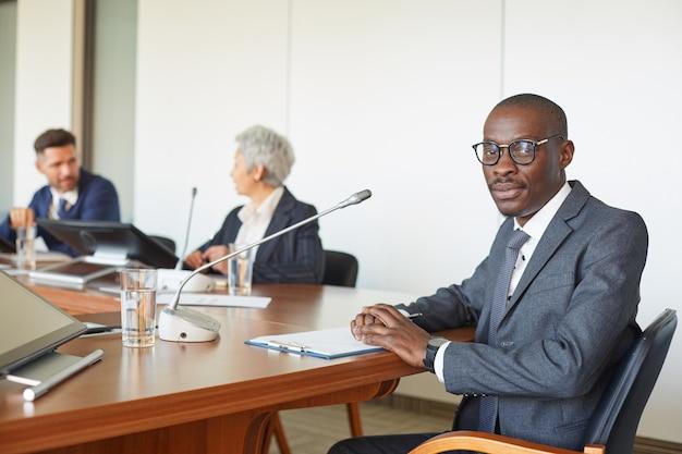 Retrato de líder africano mirando mientras está sentado a la mesa con gente de negocios en la sala de juntas