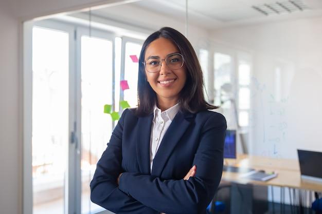 Retrato de líder empresarial latino confiado. joven empresaria en traje y gafas posando con los brazos cruzados, mirando a cámara y sonriendo. concepto de liderazgo femenino