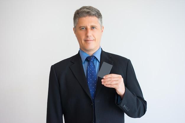 Retrato del líder serio que muestra la tarjeta de visita