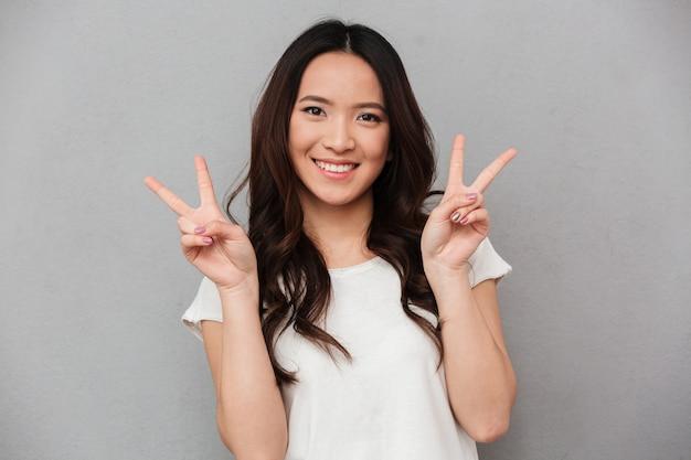 Retrato de linda chica asiática 20s en camiseta casual y jeans sonriendo y mostrando el signo de la paz con ambas manos, aislado sobre la pared gris