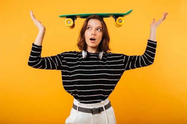 Retrato de una linda chica balanceando patineta sobre su cabeza