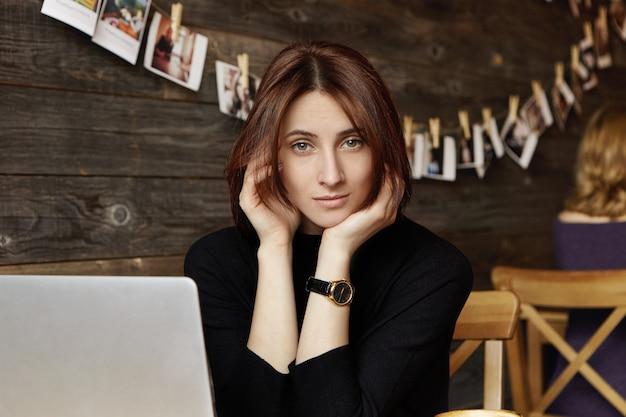 Retrato de una linda chica morena elegante con reloj de pulsera sentado frente a la computadora portátil, navegar por internet, usar conexión inalámbrica gratuita en un restaurante moderno, esperando que un amigo se una a ella para almorzar
