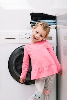 Retrato de una linda chica de pie delante de la lavadora