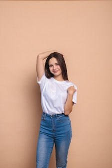 Retrato de una linda chica de piel limpia que se endereza el pelo con las manos. chica elegante en jeans y una chaqueta blanca