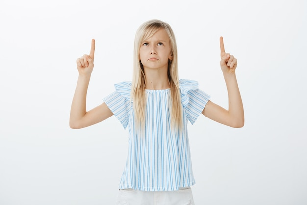 Retrato de una linda chica rubia decepcionada ofendida con blusa azul, mirando y apuntando hacia arriba con los dedos índices, frunciendo el ceño por las emociones disgustadas, viendo a la persona que no le gusta sobre la pared gris