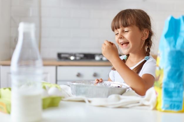 Retrato de linda chica tomando hornear, con expresión facial feliz, vestida con camiseta blanca casual, posando interior contra el juego de cocina, lista para degustar un delicioso postre.