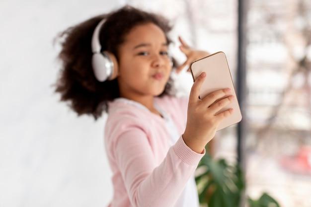 Retrato de linda chica tomando un selfie mientras escucha música