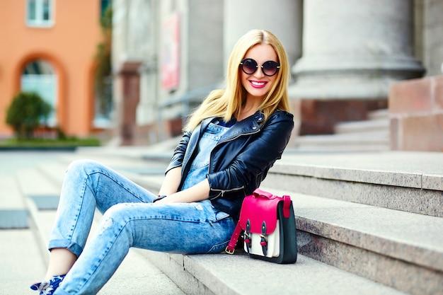 Retrato de linda divertida moderna sexy urbano joven elegante mujer sonriente modelo de niña en tela moderna brillante al aire libre sentado en el parque en jeans en un banco de gafas con bolsa rosa