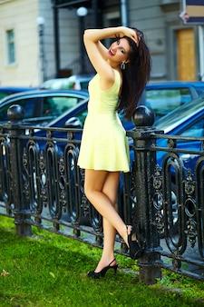 Retrato de linda divertida sexy joven elegante mujer sonriente modelo de niña en vestido amarillo moderno brillante con cuerpo perfecto bronceado al aire libre en el parque