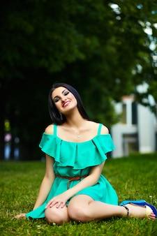 Retrato de linda divertida sexy joven elegante mujer sonriente modelo de niña en vestido verde moderno brillante con cuerpo perfecto bronceado al aire libre en el parque